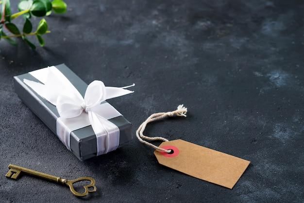 Una caja de regalo gris con una vieja llave en piedra oscura con copyspace. fiesta de san valentín