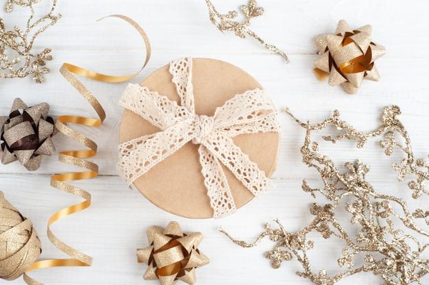 Caja de regalo y juguetes de navidad dorados sobre fondo rústico de madera
