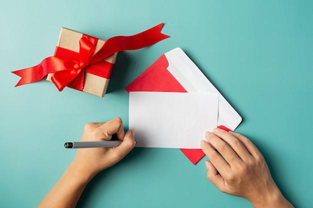 Una caja de regalo junto a la mano de la mujer está escribiendo una tarjeta de felicitación.