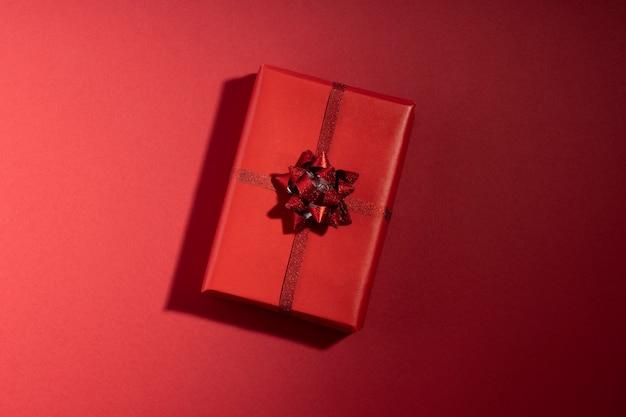 Caja de regalo con una larga sombra sobre la superficie roja. san valentín, navidad, concepto de vacaciones. vista superior, endecha plana