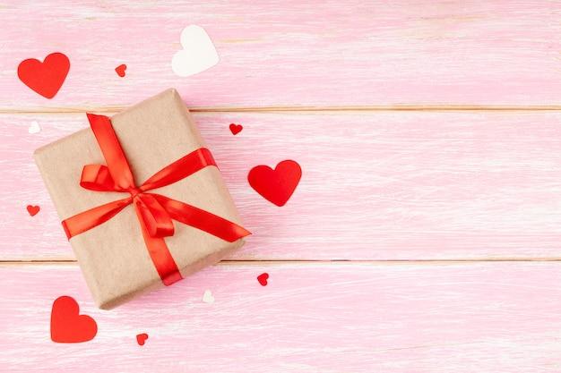 Caja de regalo con lazo de cinta roja y corazones de confeti