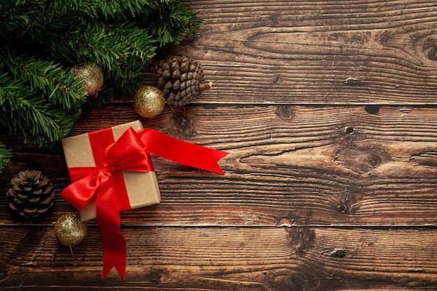 Caja de regalo con lazo de cinta roja sobre fondo de madera