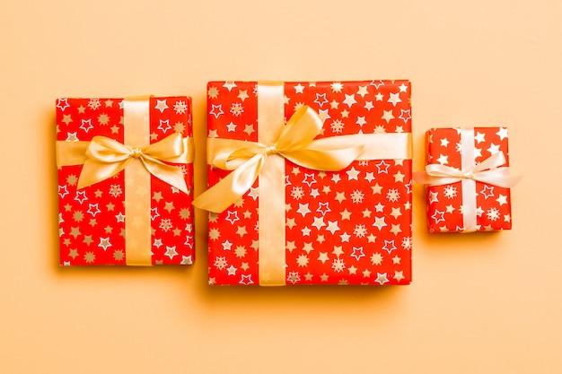Caja de regalo con lazo dorado para navidad o año nuevo sobre fondo naranja, vista superior