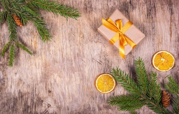Caja de regalo con lazo dorado sobre un fondo de madera con ramas de abeto