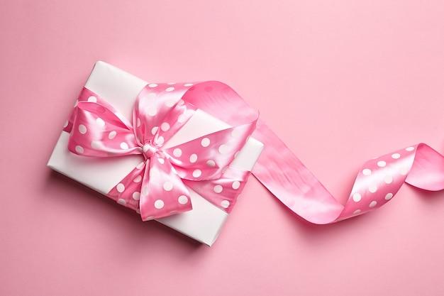 Caja de regalo con lazo grande sobre fondo rosa