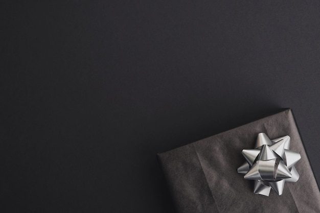 Caja de regalo con lazo plateado sobre mesa oscura. venta de viernes negro, navidad o fiesta de cumpleaños