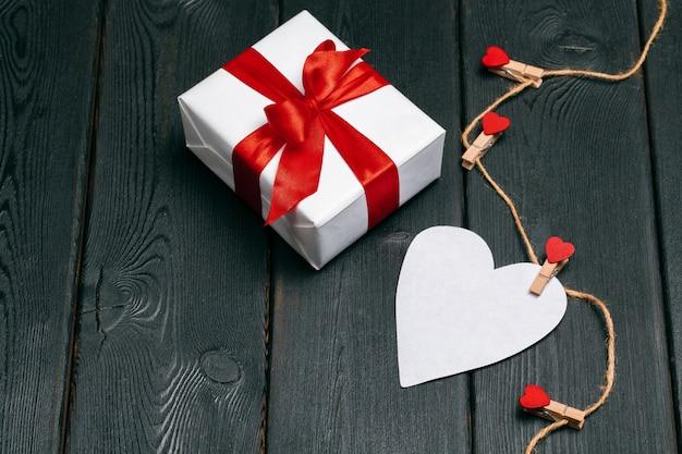 Caja de regalo con lazo rojo y corazones de papel para el día de san valentín