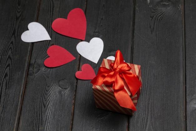 Caja de regalo con lazo rojo y corazones de papel sobre fondo de madera