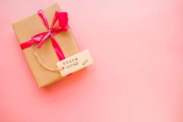 Caja de regalo con lazo rojo y etiqueta de venta.
