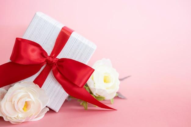 Caja de regalo con lazo rojo sobre un fondo rosa.