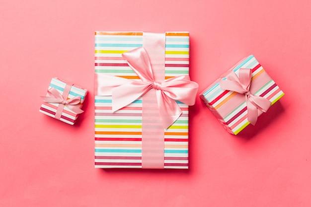 Caja de regalo con lazo rosa para navidad o año nuevo sobre fondo coral vivo