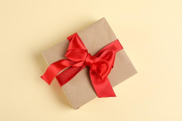 Caja de regalo con lazo sobre fondo de color, espacio para texto
