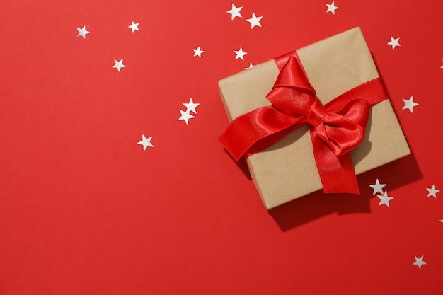 Caja de regalo con lazo sobre fondo rojo, espacio para texto