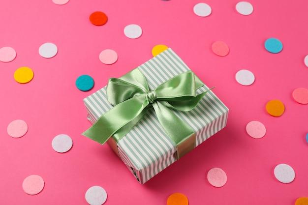 Caja de regalo con lazo sobre fondo rosa, espacio para texto