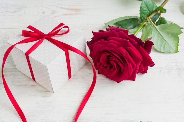 Caja de regalo de lunares beige con lazo de cinta roja y rosas rojas bautiful sobre fondo de madera. tarjeta de felicitación para vacaciones.