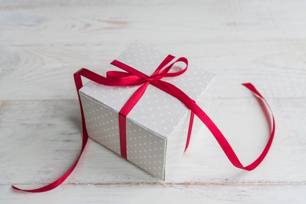 Caja de regalo de lunares beige con lazo de cinta roja sobre fondo de madera con espacio de copia.