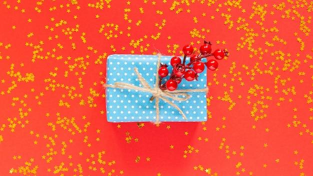 Caja regalo en lunares con cinta y lazo y una ramita de espino sobre fondo rojo con estrellas doradas brillantes