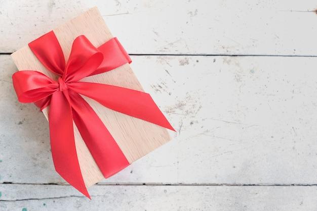 Caja de regalo de madera con arco de cinta roja sobre fondo vintage