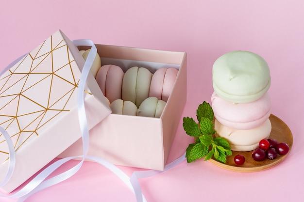 Caja de regalo con malvaviscos caseros de varios colores pastel. céfiro de manzana en forma redonda. delicioso postre de frutas sobre fondo rosa.