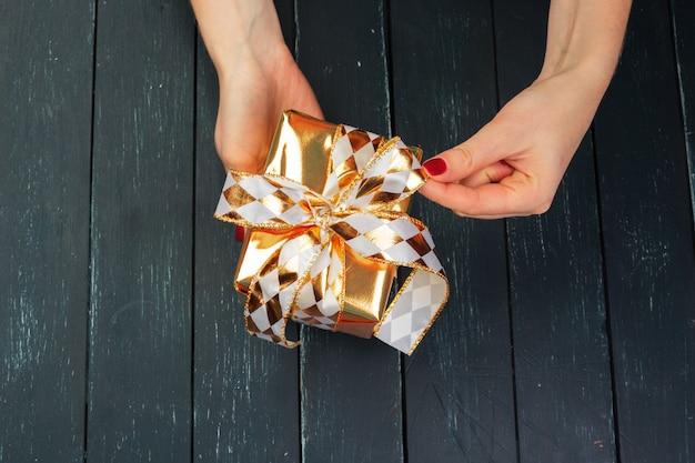 Caja de regalo en mano chicas en mesa de madera