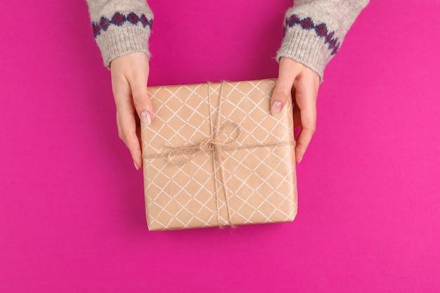 Caja de regalo en manos femeninas sobre fondo rosa