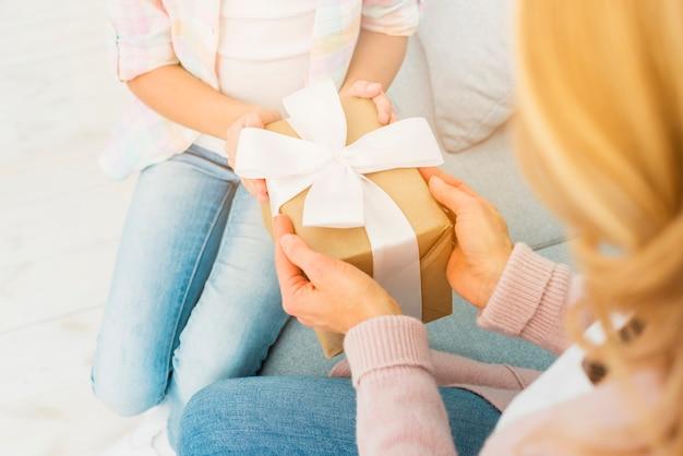 Caja de regalo en manos de madre e hija.