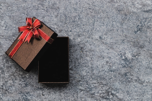 Caja de regalo marrón y un arco dorado que está abierto, colocado sobre una mesa de piedra gris