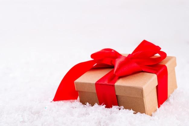 Caja de regalo marrón decorativa con un gran lazo rojo de pie en la nieve fresca
