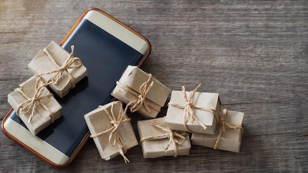 Caja de regalo de muchos papeles pequeños puestos en el móvil y suelo de madera.