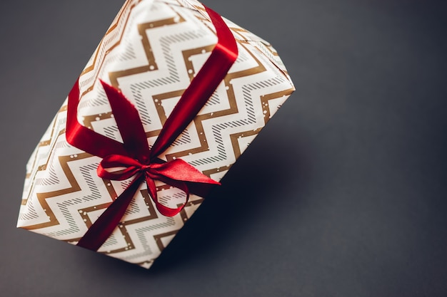 Caja de regalo de navidad y año nuevo envuelta en papel festivo y decorada con cinta roja