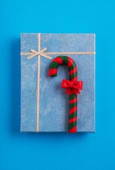 Caja de regalo de navidad azul decorada con un bastón de caramelo en el fondo azul.