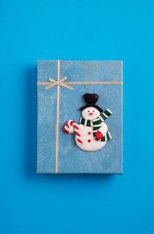 Caja de regalo de navidad azul decorada con un muñeco de nieve en el fondo azul.