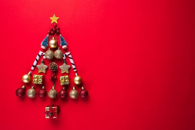 Caja de regalo de la navidad, bola roja y campana en la forma del árbol de navidad, fondo rojo.