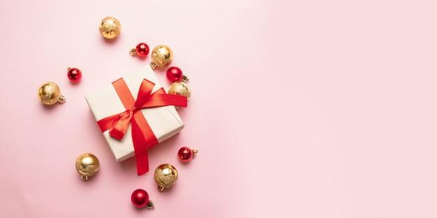 Caja de regalo de navidad con cinta de raso roja, bolas doradas y rojas en un rosa. endecha plana, vista superior, copyspace