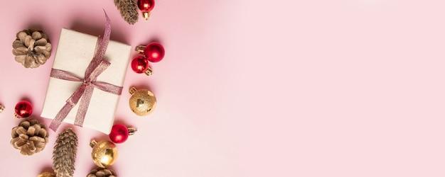 Caja de regalo de navidad con cinta roja, piña, bolas doradas y rojas en un rosa.