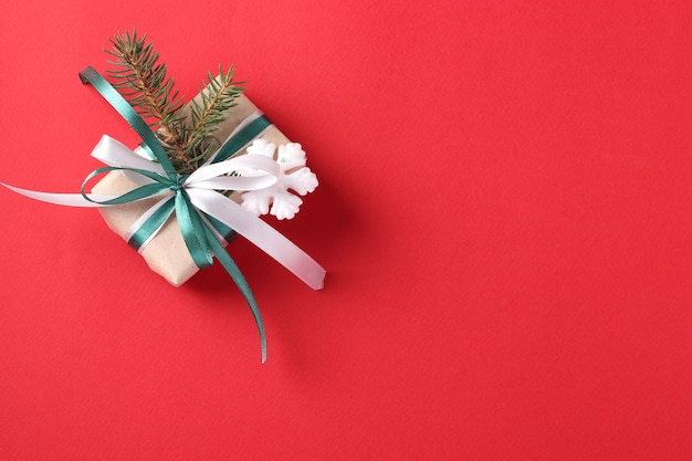 Caja de regalo de navidad con cintas verdes y blancas sobre superficie roja. espacio para deseos.