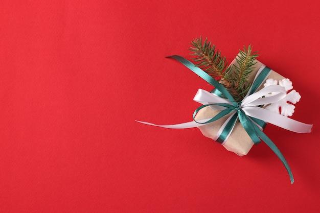 Caja de regalo de navidad con cintas verdes y blancas sobre superficie roja
