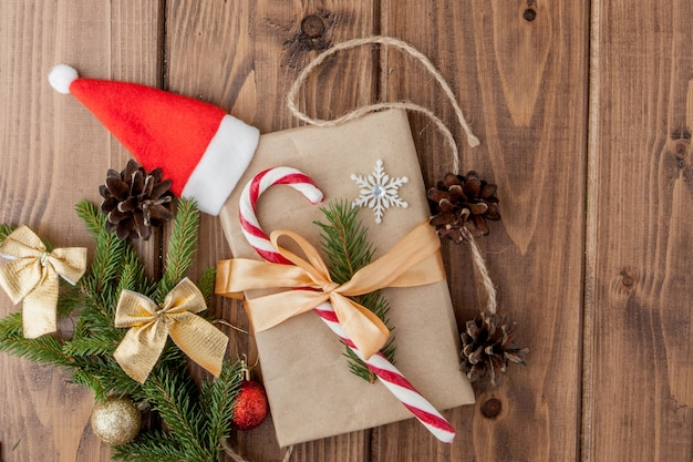 Caja de regalo de navidad, decoración de alimentos y rama de abeto en mesa de madera. vista superior con copyspace