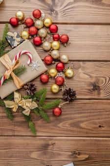 Caja de regalo de navidad, decoración de alimentos y rama de abeto en mesa de madera