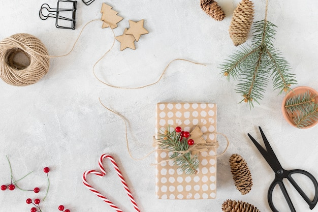 Caja de regalo de navidad con decoración en mesa gris.