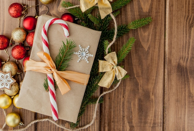 Caja de regalo de navidad, decoración y rama de abeto en mesa de madera. vista superior con copyspace