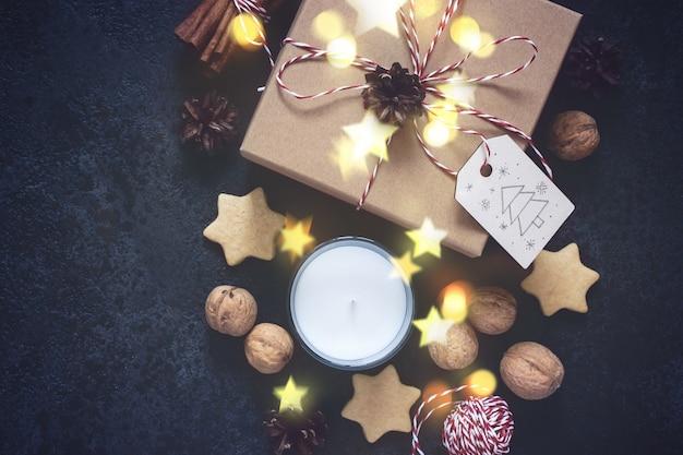 Caja de regalo de navidad y decoraciones navideñas sobre fondo negro