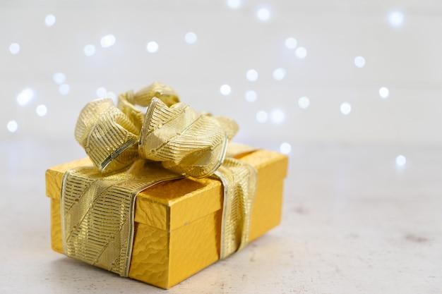 Caja de regalo de navidad dorada con arco, foco superficial