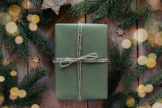 Caja de regalo de navidad envuelta en papel kraft verde y decorada con rama de pino sobre fondo festivo de año nuevo