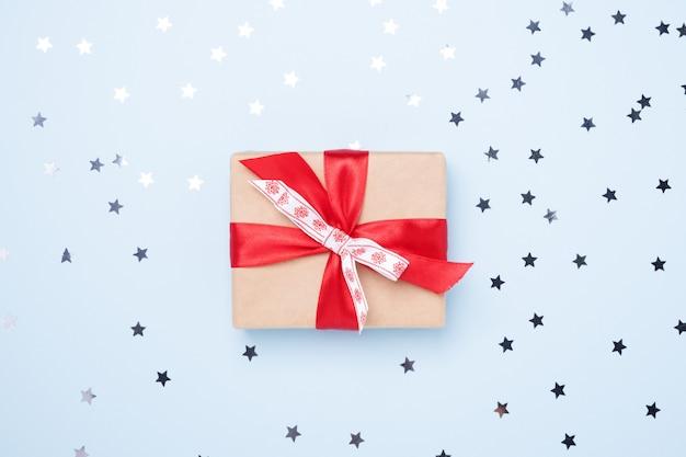 Caja de regalo de navidad con estrellas de confeti sobre fondo azul.