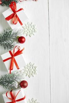 Caja de regalo de navidad, ramas de abeto, adornos rojos sobre fondo blanco de madera, navidad, invierno, concepto de año nuevo, endecha plana, vista superior, espacio de copia