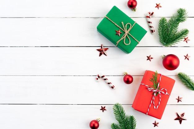 Caja de regalo de navidad, ramas de abeto, bola roja sobre fondo de madera