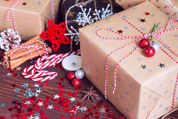 Caja de regalo navideña en una mesa festiva decorada con piñas, canela, caramelo, nueces y estrellas de destellos sobre fondo de madera
