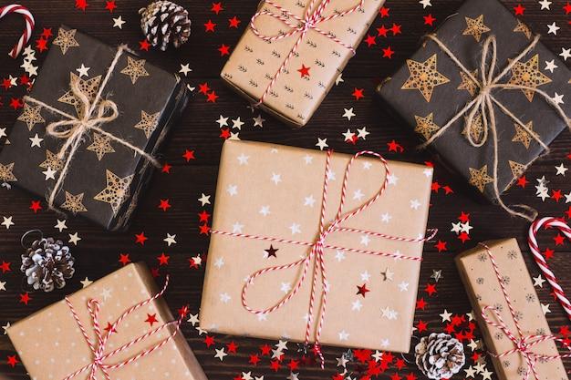 Caja de regalo navideña en una mesa festiva decorada con piñas y estrellas brillantes
