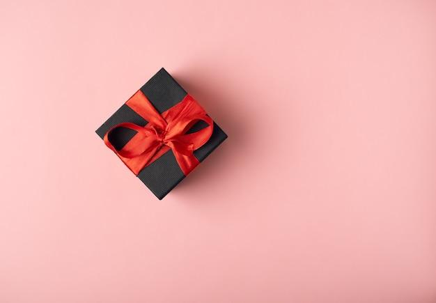 Caja de regalo negra atada con una cinta roja. concepto de san valentín. vista plana endecha, superior.